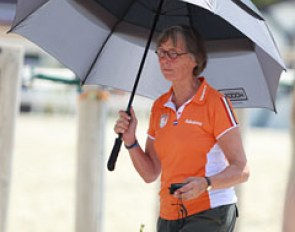 Dutch team trainer Tineke Bartels uses an umbrella to protect herself from the sun