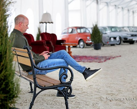 Hans Peter Minderhoud taking a break with the classic car show in the background