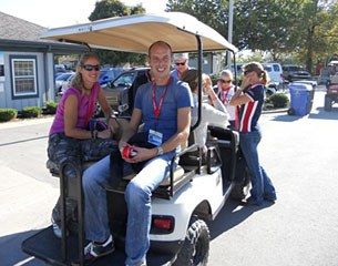 Adelinde Cornelissen and Hans Peter Minderhoud share a ride on the golfcart