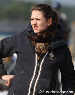 Dog using owner and her coat as windbreaker